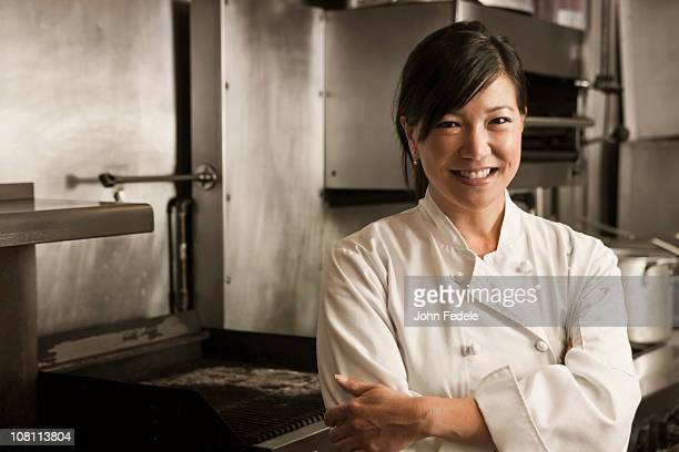 Smiling Chinese chef standing in commercial kitchen