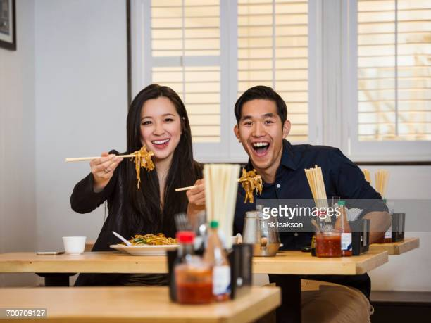 Smiling Chinese couple holding noodles with chopsticks in restaurant