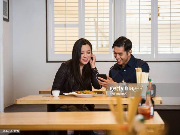 Smiling Chinese couple listening to cell phone in restaurant