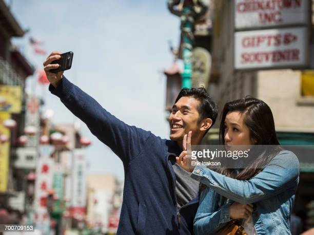 Smiling Chinese couple posing for cell phone selfie in city