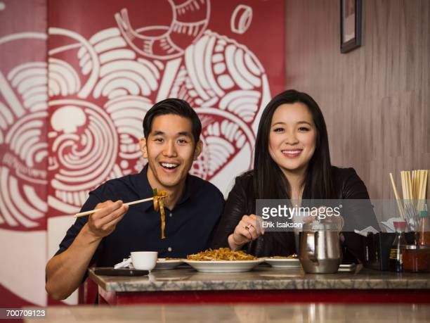 Smiling Chinese couple posing in restaurant