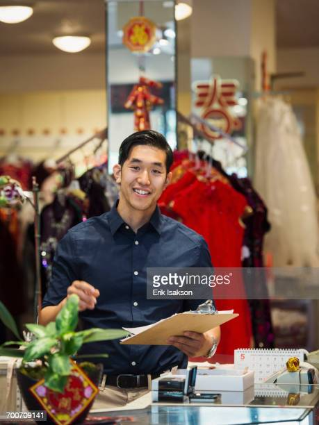 Smiling Chinese man writing on clipboard in store