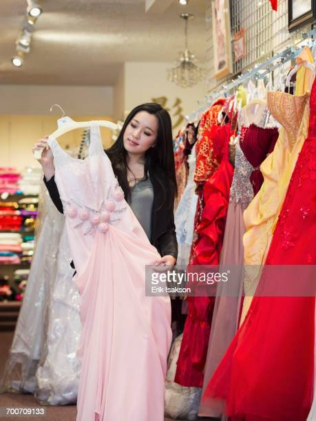 Smiling Chinese woman shopping for dress