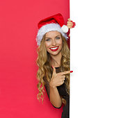 Smiling young blond woman in santa's hat and black dress standing behind white placard and pointing. Waist up studio shot on red background.