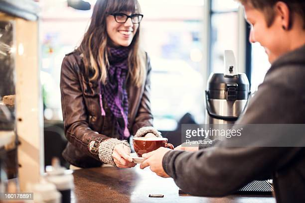 Smiling coffee shop worker hands latte to customer