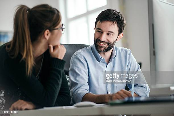 Smiling collaegues talking at office desk
