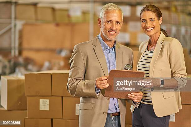 Smiling colleagues in a warehouse and going through check list