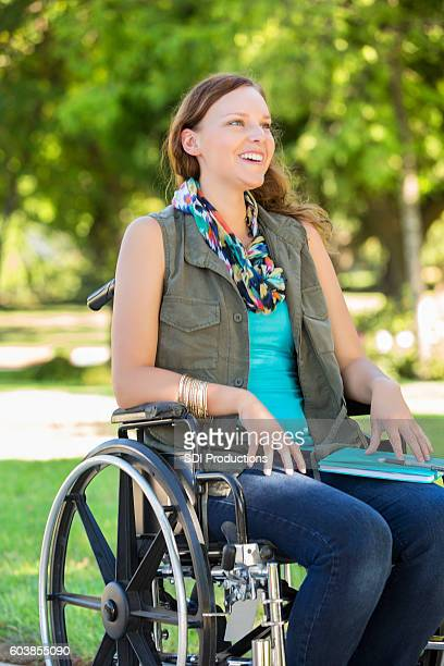 Smiling college girl in wheelchair on campus
