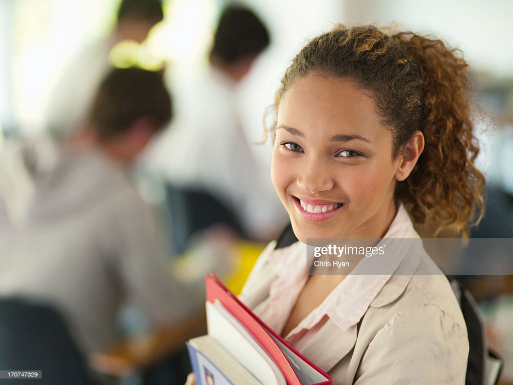 Smiling college student holding books