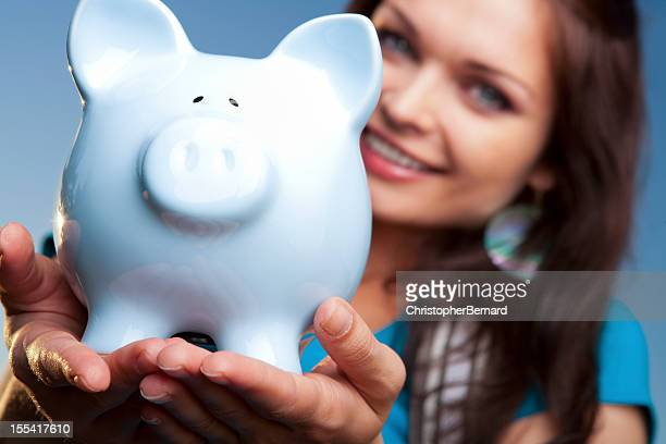 Smiling college student with blue piggy bank