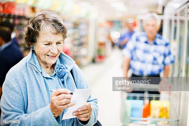 Smiling confident senior woman checks shopping list in supermarket