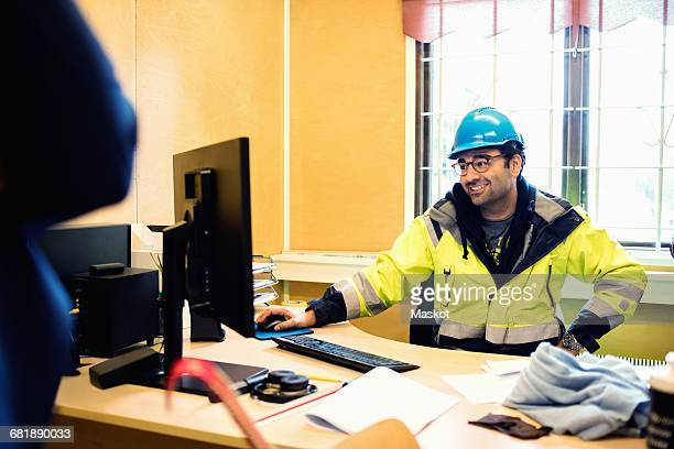 Smiling construction worker in protective wear talking to man while sitting at desk
