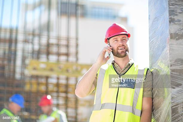 Smiling construction worker on cell phone