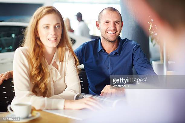 Smiling couple at car dealer