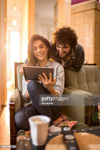 Smiling couple at home using touchpad.