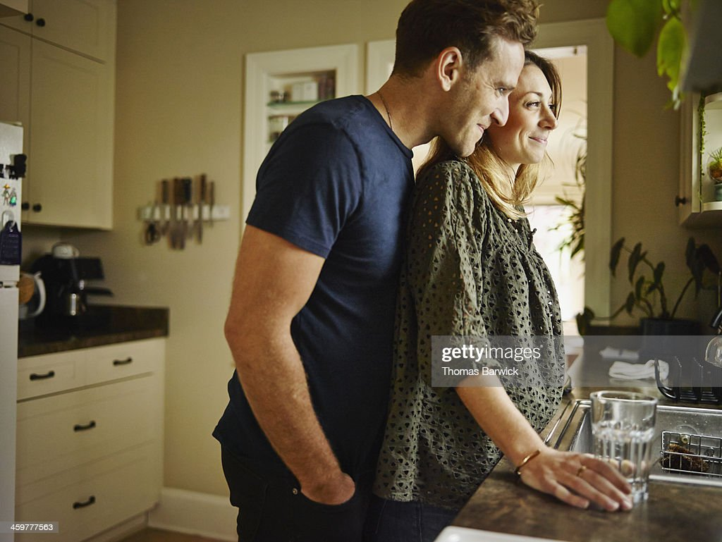 Smiling couple at kitchen sink looking out window : Stockfoto