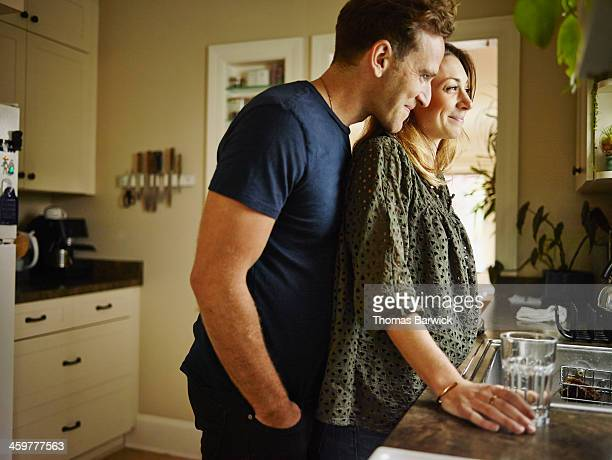 Smiling couple at kitchen sink looking out window