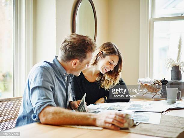 Smiling couple at table in home reading newspaper