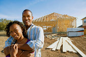 Smiling couple by house being constructed
