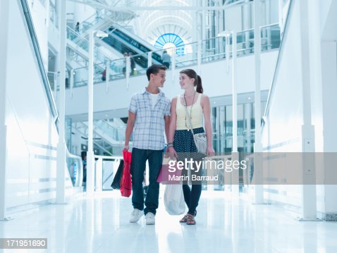 Smiling couple carrying shopping bags in mall : Stock Photo