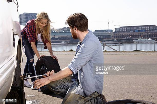 Smiling couple changing car tyre at minivan