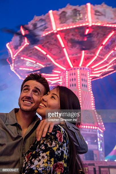 Smiling couple cheek to cheek in amusement park