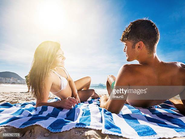 Smiling couple communicating on the beach.