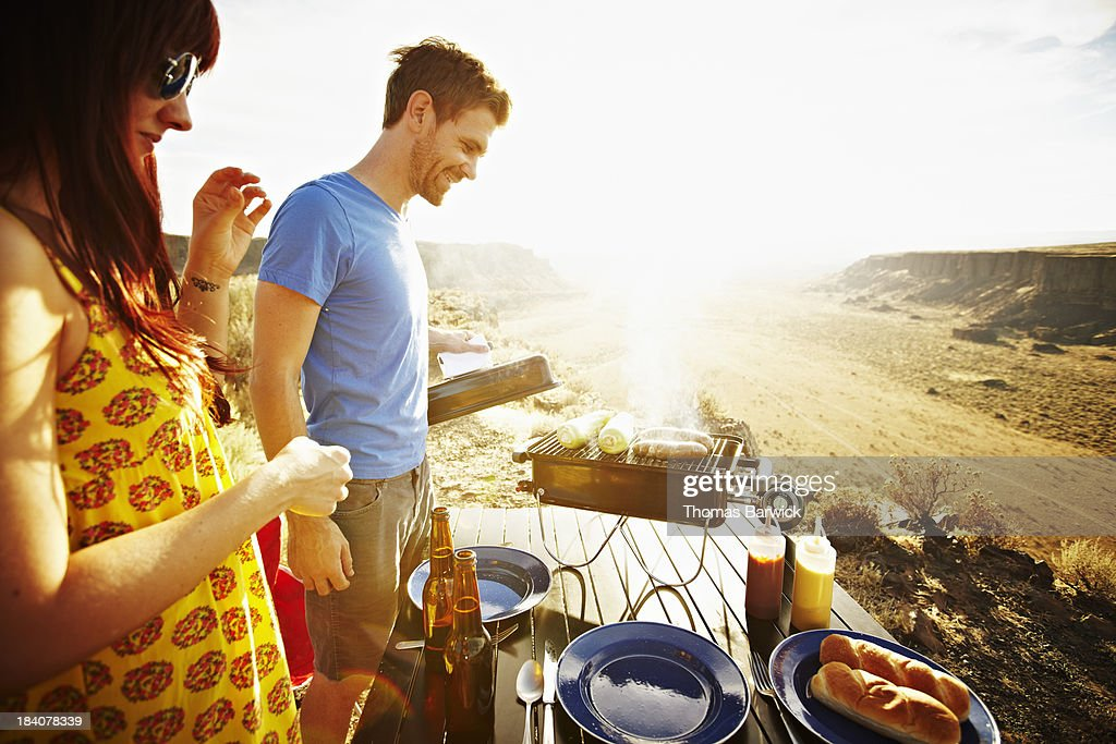 Smiling couple cooking on barbecue at sunset : Stock Photo