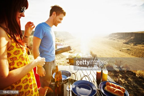 Smiling couple cooking on barbecue at sunset