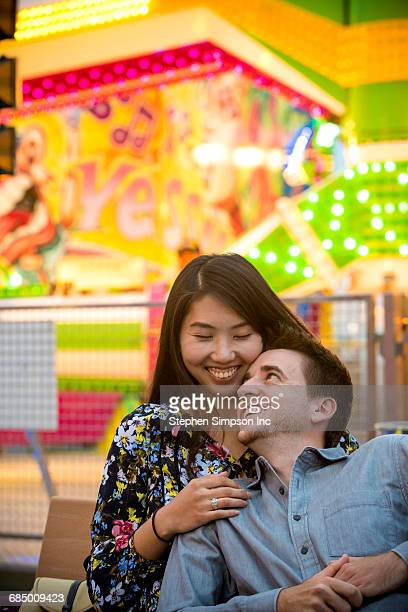 Smiling couple cuddling on bench in amusement park