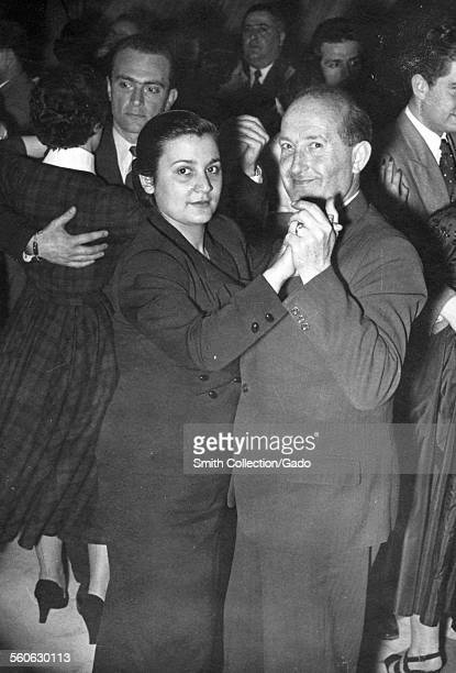 A smiling couple dancing in a ballroom people in the background woman wearing a dark dress man a suit Germany 1946