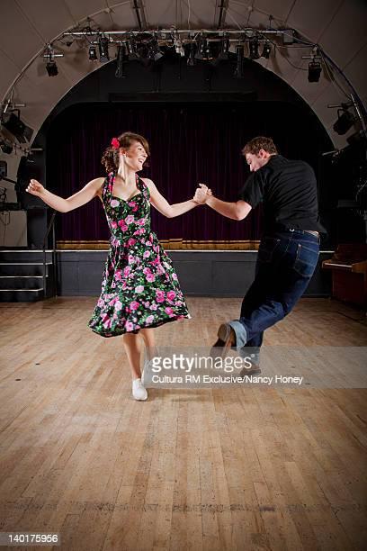 Smiling couple dancing in auditorium