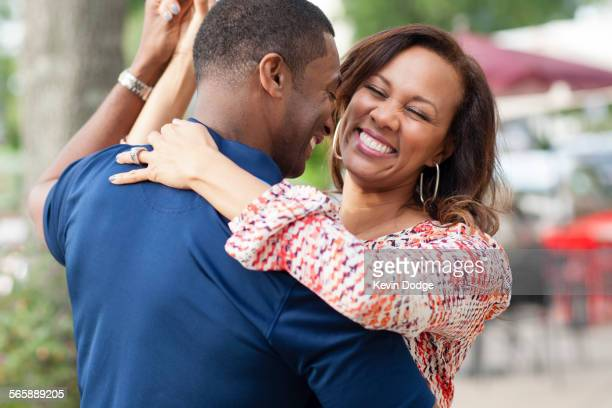 Smiling couple dancing on sidewalk