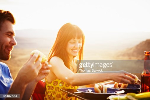 Smiling couple dining at table at sunset