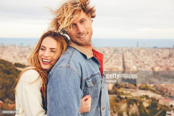 Couple souriant embrassant contre cityscape