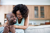 Smiling couple embracing each other in living room at home