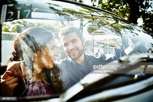 Smiling couple embracing in convertible