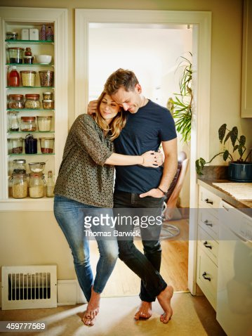 Smiling couple embracing in doorway of kitchen
