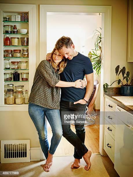 Smiling couple embracing in doorway of kitchen