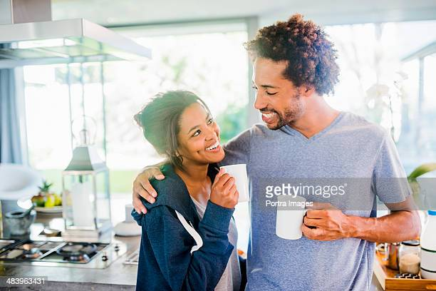 Smiling couple embracing in the kitchen