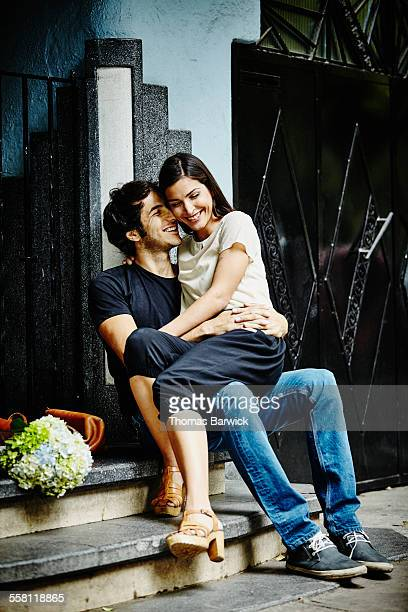 Smiling couple embracing on steps of building