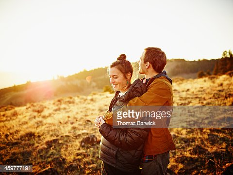 Smiling couple embracing watching sunset