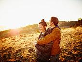Smiling couple embracing watching sunset