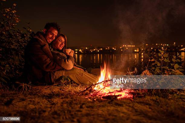 Smiling couple enjoying in campfire during the night.
