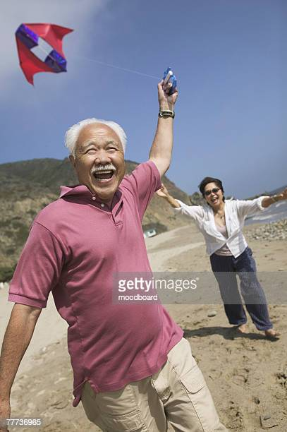 Smiling Couple Flying Kite on Beach