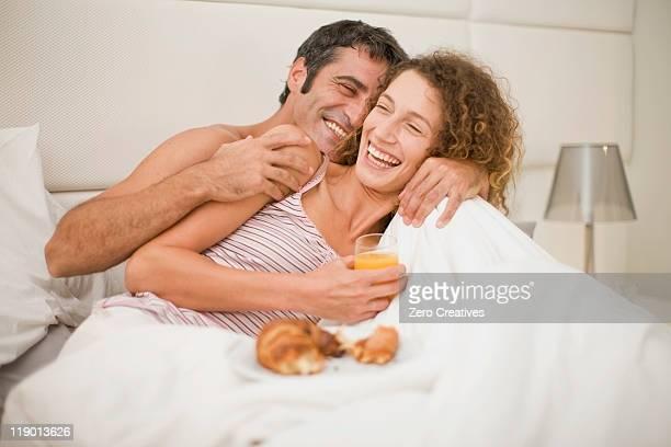 Sorridente Casal tendo o pequeno-almoço na cama
