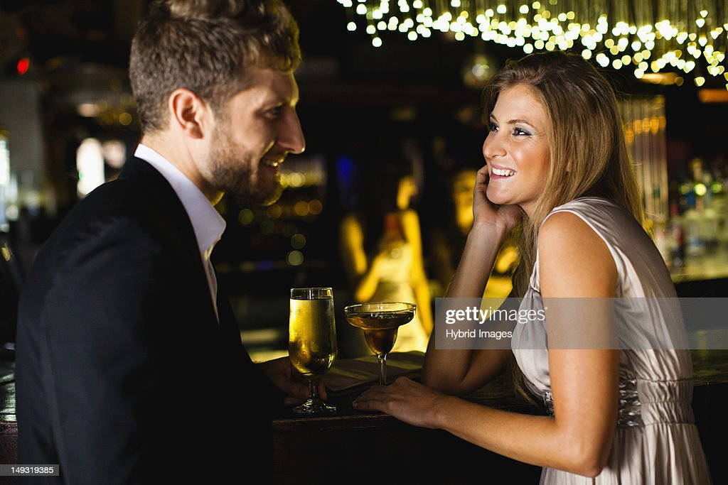 Smiling couple having drinks at bar : Stock Photo