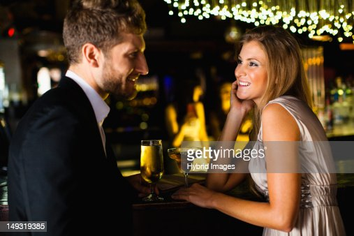 Smiling couple having drinks at bar