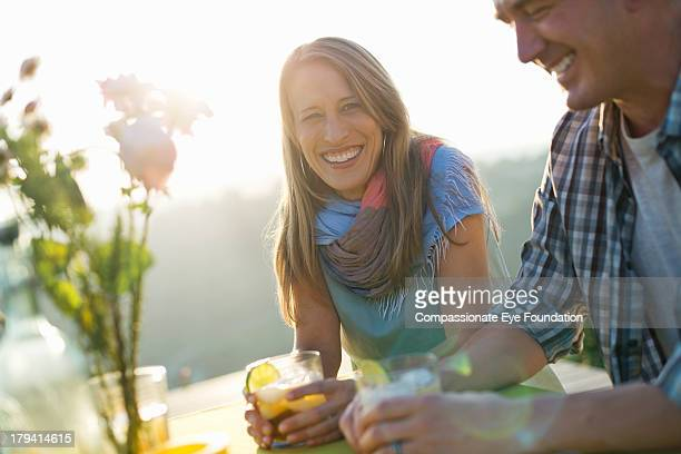 Smiling couple having drinks outdoors