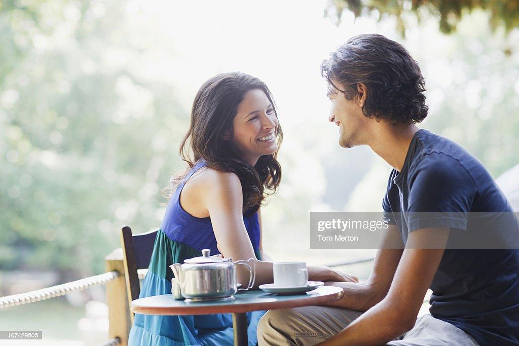 Smiling couple having tea outdoors : Stock Photo